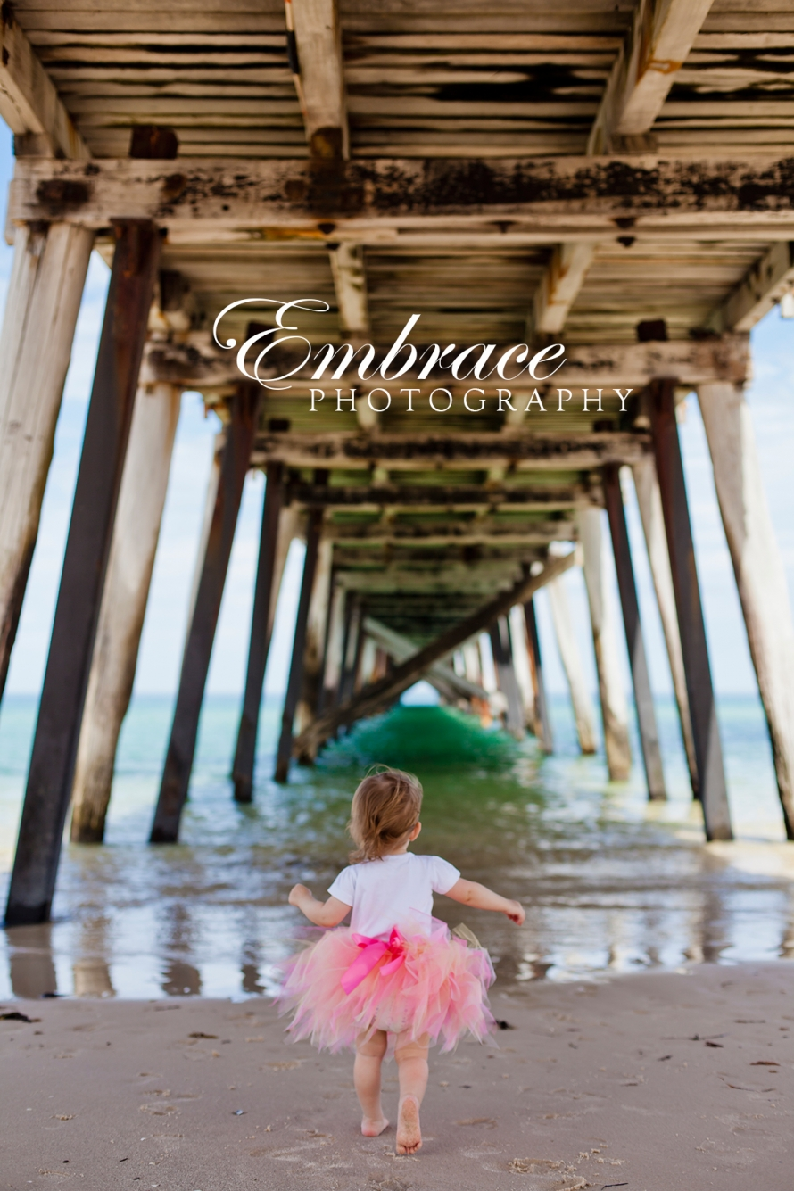 girl-under-jetty-beach-adelaide-family-photographer-embrace-photography